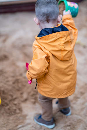 Young Boy Playing in Sand Box, Vertical Photo from Behind with Selective Focus