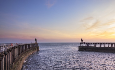 costal: Sunrise looking out to sea from the pier at Whitby Stock Photo