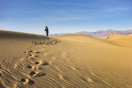hushed: Woman walking along through the rippling golden sand of Mesquite Flat Dunes, Death Valley