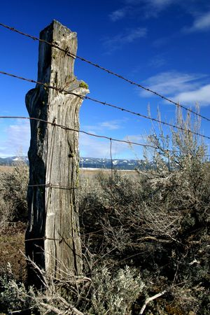 fencepost: Rustic wooden fence post in rural Idaho Stock Photo