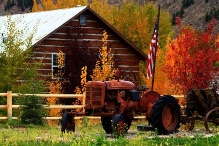 Rusty tractor sits in autumn color with U.S. flag Stock Photo