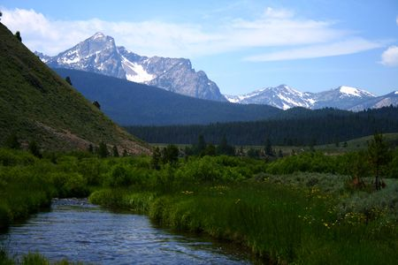 stanley: Stanley Creek as it flows through high mountain meadow,Sawtooth Mountains in background, Stanley Idaho Stock Photo