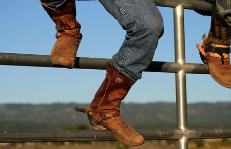 worn: Well worn boots adorn the wranglers at rodeo in small county fair, Idaho