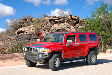Beautiful red Hummer parked in a beautiful desert setting with natural rocks in the background.