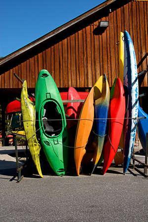 rentals: Colorful Kayaks stacked and waiting .