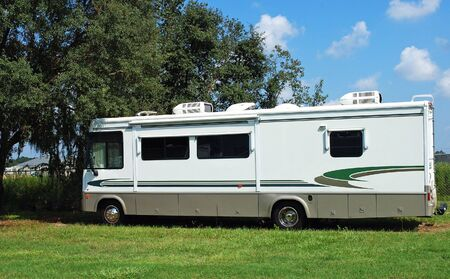 motor home: RV parked in the shade of a tree. Stock Photo