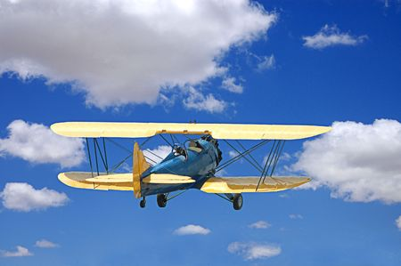 Biplane flying through puffy white clouds in a blue sky with two aviators. Imagens