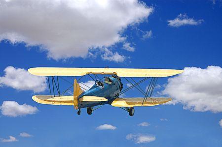 pilotos aviadores: Biplano que volaba a través de puffy nubes blancas en un cielo azul con dos aviadores.