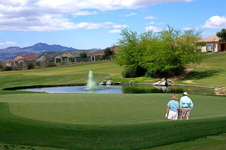 Two golfers on the green studying the pitch at a restricted communitys golf course in Tucson, Arizona with the mountains in the background.