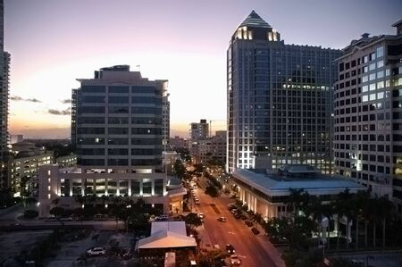 Cityscape at dusk with office buildings and light traffic on Las Olas Boulevard in Fort Lauderdale, Florida.