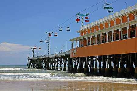 vacationers: Oceanside pier extending out into the ocean with a scenic chair lift. Stock Photo