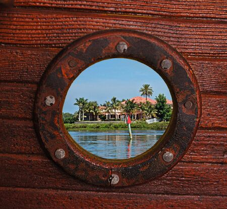 riverfront: Unusual rustic porthole view of beautiful palms, riverfront homes and river.