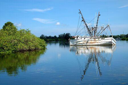 listing: Este buque de ostras fue severamente da�ado por una tormenta y est� lista para su starbor lado en el canal en Tarpon Springs, Florida.