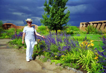 lesure: Woman enjoying a plush spanish garden and archetecture in New Mexico Stock Photo