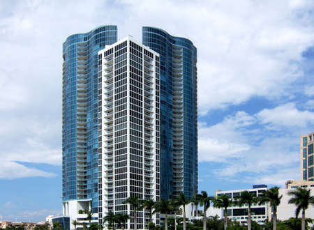 towering: Hi-rise condominium jutting up into the sky towering over  palm trees below.