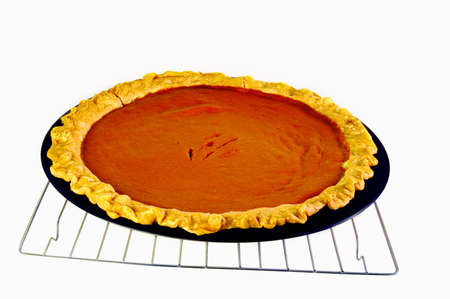 Delicious, hot pumpkin pie cooling down on a grate appears appetizing.