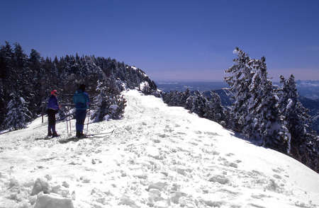 Cross country skiers on top of sandia mountain enjoying the view