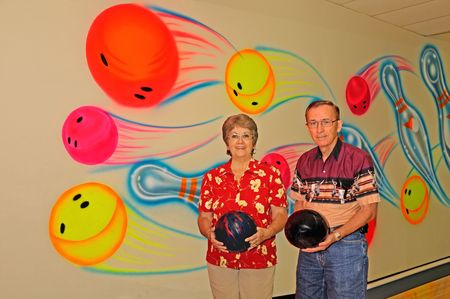 Two bowlers with bowling balls against a colorful wall at the alley.