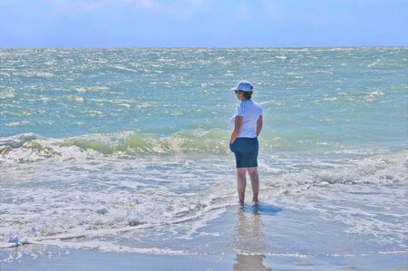 cool off: Woman wading in the surf to cool off on a hot day
