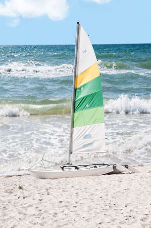 forground: Rough surf with sail boat in the forground on a beach of white sand