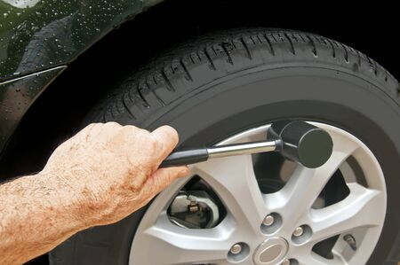 chrome man: Man using a rubber mallet to secure a wheel cover