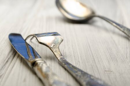grunge flatware: old cutlery on white wooden table in different positions Stock Photo