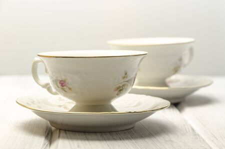 teacups: two stylish antique teacups on white background