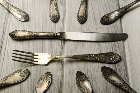 modish: old cutlery on white wooden table in different positions Stock Photo