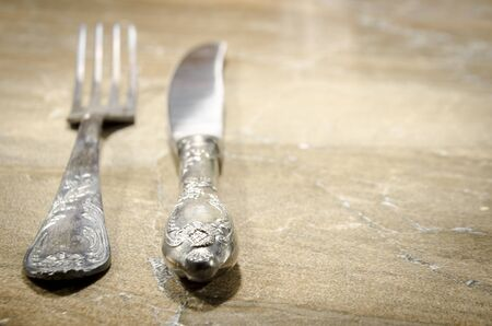 grunge cutlery: old cutlery on marble table in different positions