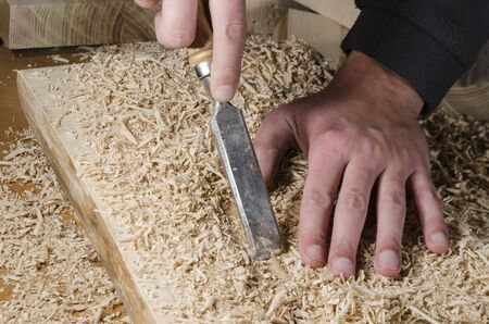 carpenter's bench: joinery tools - chisel on wooden table with sawdust