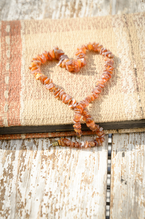 photo album: Old photo album with heart created from amber necklace