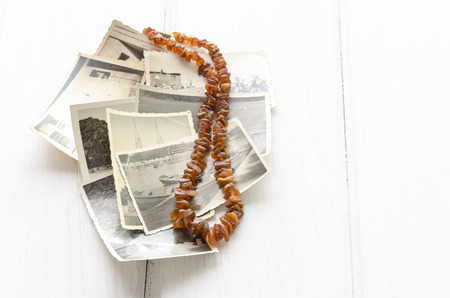 archival: Stack of old photographs with amber necklace and copy space