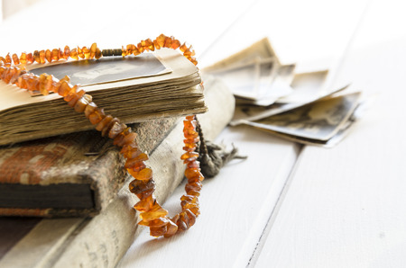Stack of old photographs with amber necklace on photo album Stock Photo