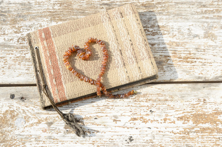 archival: Old photo album with heart created from amber necklace