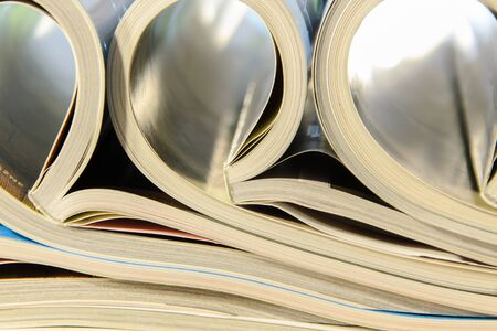 side view of a stack of magazines with glossy paper