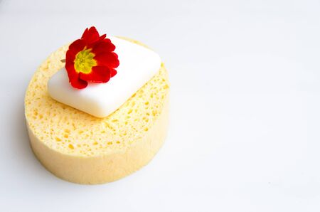 used white soap bar on a yellow sponge placed on a white background with space for text