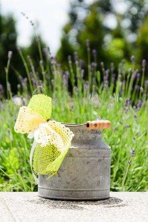 Rustic milk can with green ribbon Stock Photo