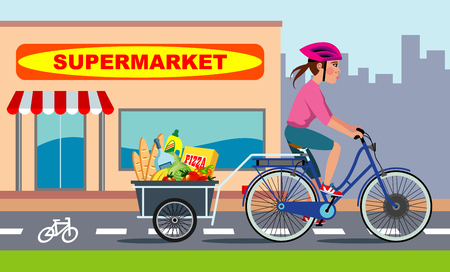 Ragazza in sella a una bici elettrica con un rimorchio pieno di generi alimentari, corre lungo una pista ciclabile Archivio Fotografico - 92092640