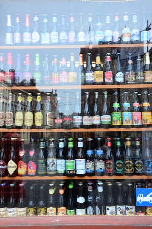 ranging: Gent, Belgium - May 16, 2016: Shop window with lots of Belgium beer types. There are approximately 180 breweries in the country, ranging from international giants to microbreweries.