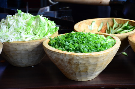Sliced, chopped spring onions, salad onions, green onions or scallions in a wood bowl. Stock Photo