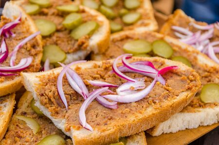 Slices of bread with lard greaves and onion topping