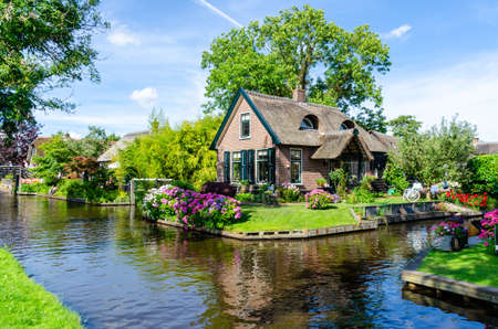 """Giethoorn, Netherlands: Landscape view of famous Giethoorn village with canals and rustic thatched roof houses. The beautiful houses and gardening city is know as """"Venice of the North"""". Banque d'images"""