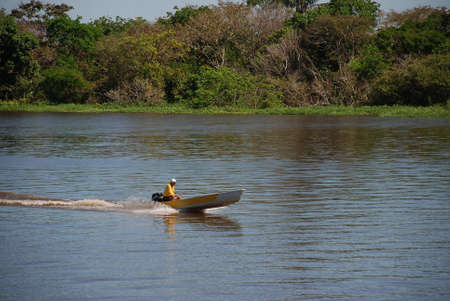 A villager travelling along the River Amazon near Manaus in a motor boat Publikacyjne