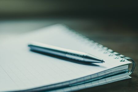 Ball point pen on spiral note pad.,posed on wooden desk,selective focus.