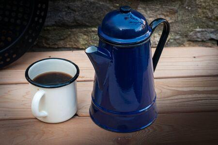Old enamel coffee mug and blue pot. outside on wood table against stone wall. Standard-Bild