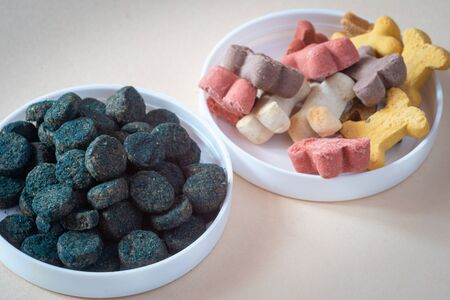 Dog treats and spirulina for pets, in small bowls, pale background. Training & healthy animals.
