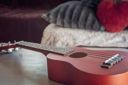 red ukulele on table with cosy room in background Banco de Imagens