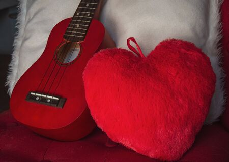 ukulele on chair with red heart cushion  concept I love music ,cosy warm weekend. Banco de Imagens