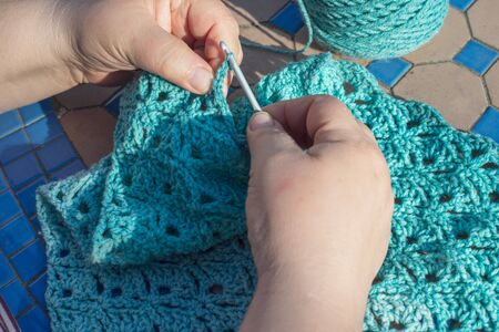 Woman making a blue shawl or scarf with crochet hook in garden at home.