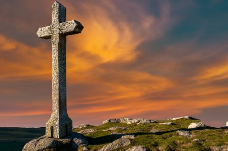 Stone cross against beautiful sunset; copy space concept belief.Religion  easter.